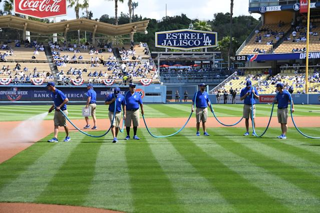 """Dodgers groundskeepers work on the field during opening day at Dodger Stadium in 2019. <span class=""""copyright"""">(Jon SooHoo / L.A. Dodgers)</span>"""