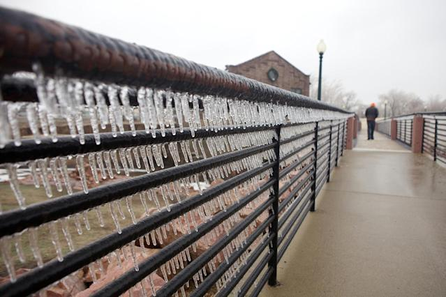 Ice accumulates on a bridge at The Falls Park in Sioux Falls, S.D., where a spring storm drove away visitors from the usually popular tourist attraction on Tuesday, April 9, 2013. The ice storm wreaked havoc on roads, downed branches and knocked out power for thousands of residents. The National Weather Service predicted that a half-inch of ice would accumulate by day's end. Other parts of the state were grappling with large amounts of snow. (AP Photo/Amber Hunt)