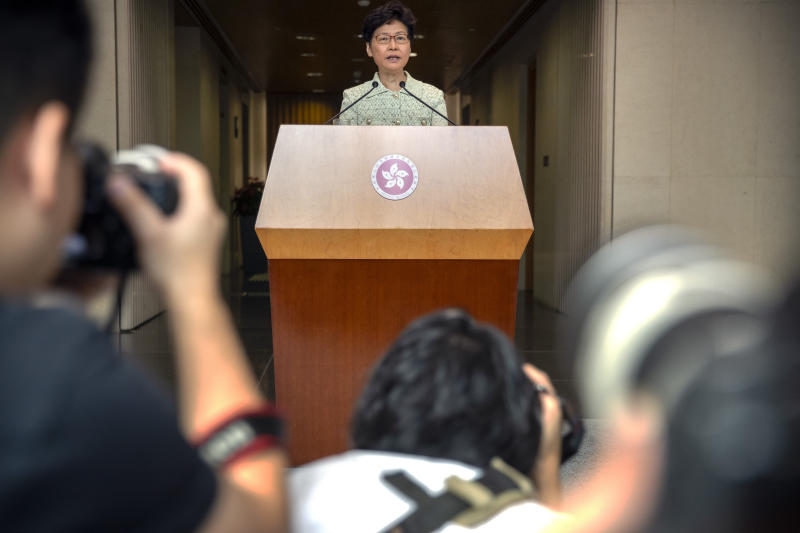 """Journalists take photos as Hong Kong Chief Executive Carrie Lam speaks during a press conference at the government building in Hong Kong, Tuesday, Oct. 15, 2019. A homemade, remote-controlled bomb intended to """"kill or to harm"""" riot control officers was detonated as they deployed against renewed violence in Hong Kong over the weekend, police said Monday, in a further escalation of destructive street battles gripping the business hub. (AP Photo/Mark Schiefelbein)"""