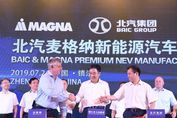Magna and BAIC executives are shown shaking hands in front of a banner with the two companies' logos and text in both English and Chinese.