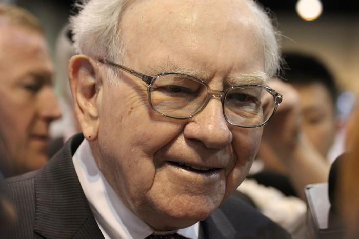 Warren Buffett smiling while standing in a huddle of people at an event.
