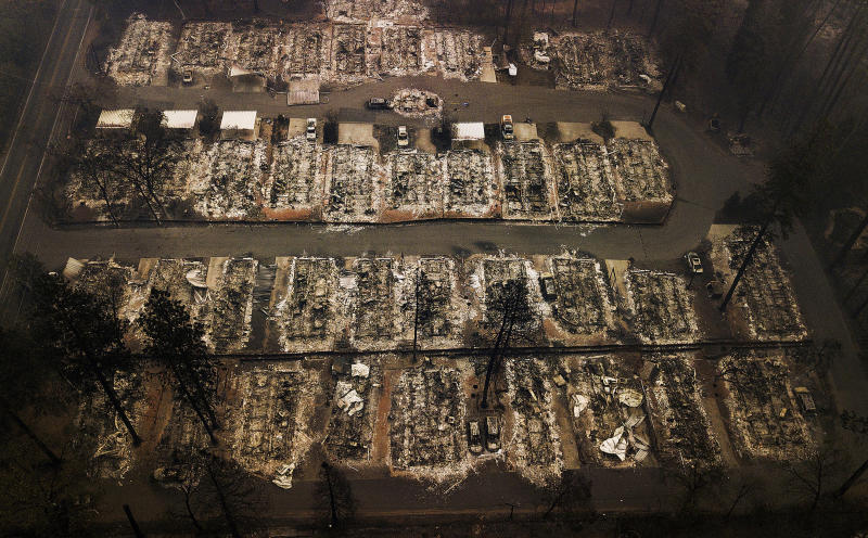 """FILE - This Nov. 15, 2018, aerial file photo shows the remains of residences leveled by the Camp wildfire in Paradise, Calif. A group of insurance companies are offering a plan to take over Pacific Gas & Electric, the latest to offer competing proposals to pay the utility's wildfire liabilities and pull it out of bankruptcy. In court filings Tuesday, July 23, 2019, the insurers said PG&E Corp. owes them more than $20 billion in claims paid to victims of recent California wildfires caused by PG&E equipment and offered a """"viable path"""" to emerge from bankruptcy. (AP Photo/Noah Berger, File)"""