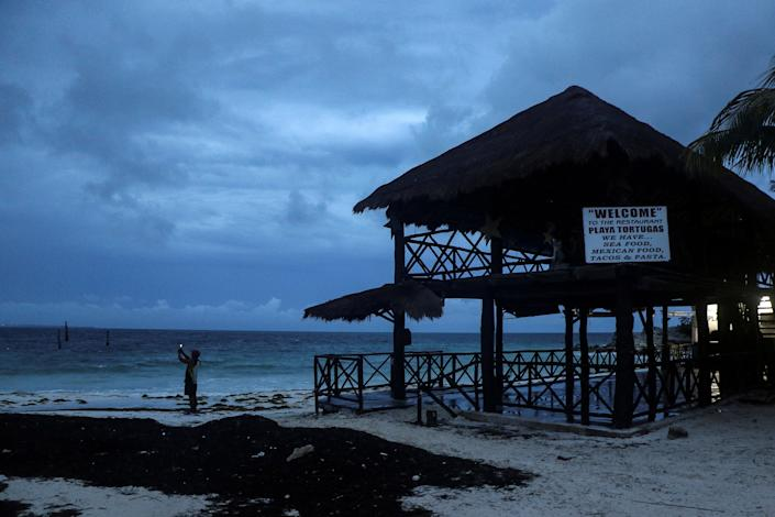 Image: A man takes a video with his phone at a beach as Hurricane Delta approaches Cancun (Jorge Delgado / Reuters)