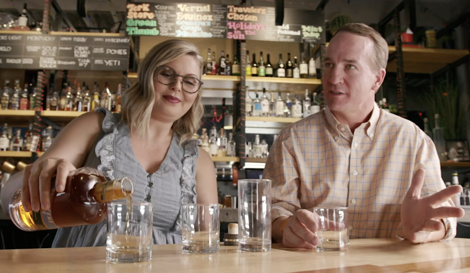 Peyton Manning sits with Marianne Eaves, master blender of Sweetens Cove Tennessee Bourbon, which Manning is launching in Indiana.