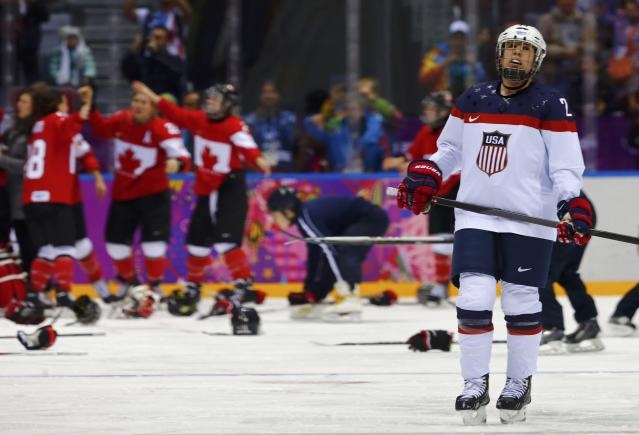 Team USA's Lee Stecklein skates away as Canada celebrates winning their women's ice hockey gold medal game at the Sochi 2014 Winter Olympic Games February 20, 2014. REUTERS/Mark Blinch (RUSSIA - Tags: OLYMPICS SPORT ICE HOCKEY)