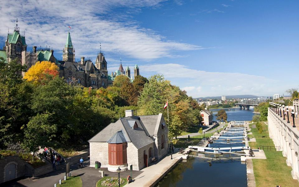 canal, trees and grand parliament building with spires - iStock