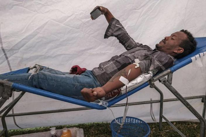 A man takes a selfie as he donates blood at the rally in Addis, organised by the city administration