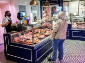 A lady shops inside Smith and Clay, a butchery and deli in Buckingham, Britain
