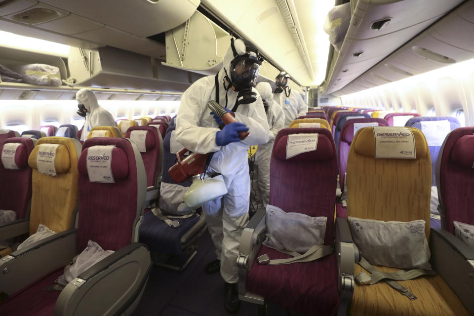 Crew members in protective suits and masks spraying during the disinfection process.