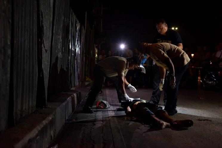 Police investigators inspect the body of a still-unidentified victim