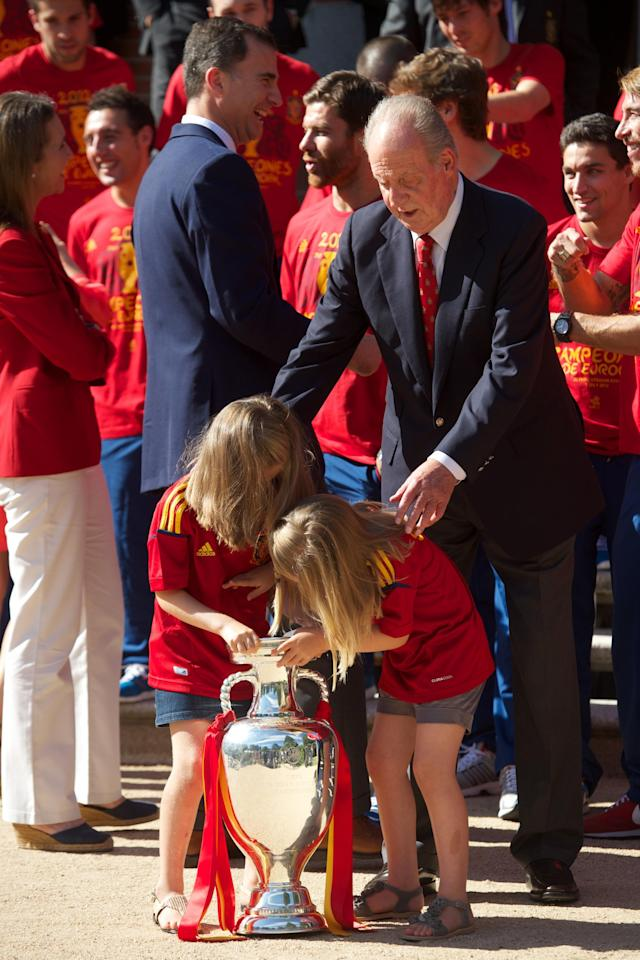 MADRID, SPAIN - JULY 02: Princess Leonor of Spain and Princess Sofia of Spain play with the UEFA EURO 2012 trophy next to King Juan Carlos I of Spain as they receive the players of the victorious Spain team at Zarzuela Palace on July 2, 2012 in Madrid, Spain. (Photo by Pool/Getty Images)