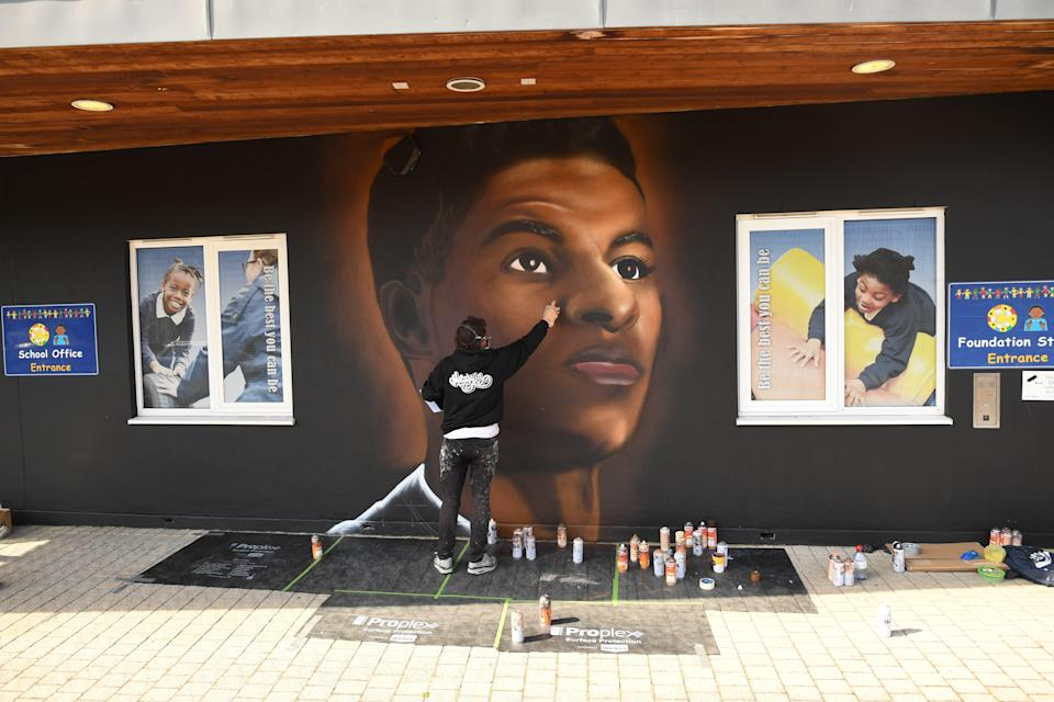 <p>Josh from street artists MurWalls paints a mural of footballer Marcus Rashford on the wall of Gainsborough Primary School</p> (PA Wire)