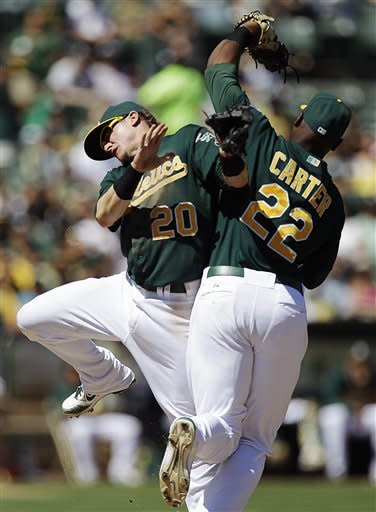 Oakland Athletics third baseman Josh Donaldson, left, collides with first baseman Chris Carter after Carter made the catch on a pop up hit by Los Angeles Angels' Albert Pujols in the fourth inning of a baseball game, Monday, Sept. 3, 2012, in Oakland, Calif. (AP Photo/Ben Margot)