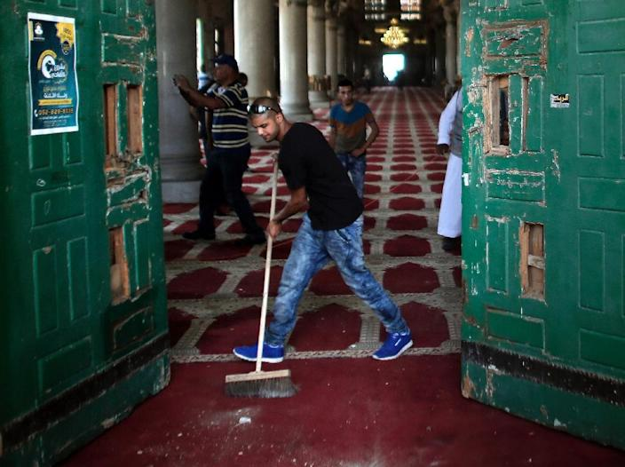 Palestinians clear the damage at the entrance of Al Aqsa Mosque in Jerusalem's Old City following clashes with Israeli riot police on September 15, 2015 (AFP Photo/Ahmad Gharabli)