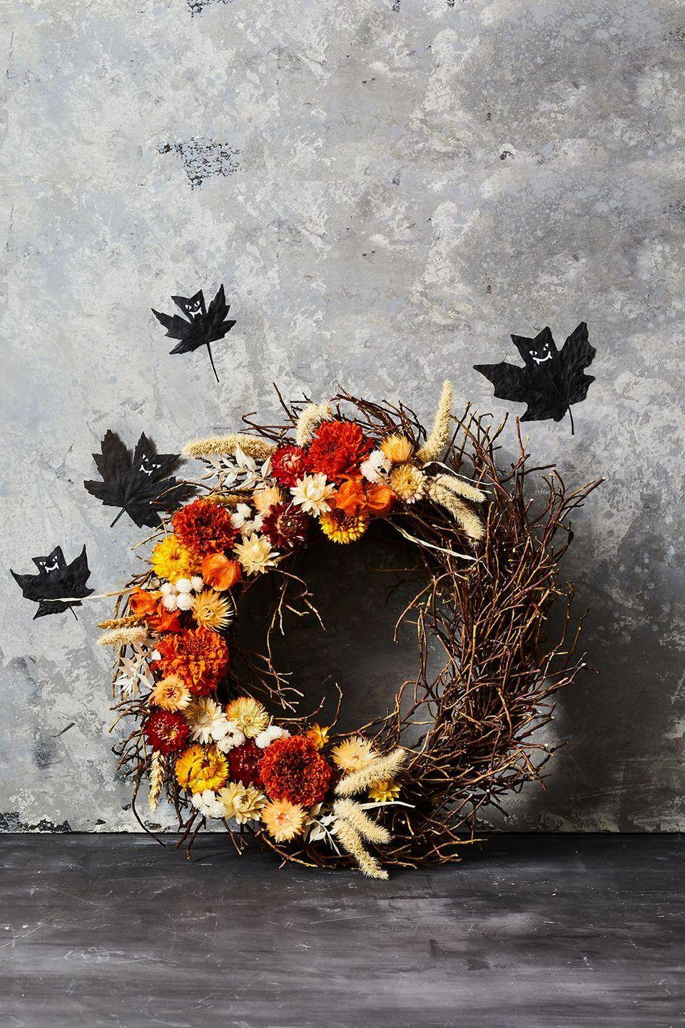 """<p>Add your leaf bats here for October, and once November comes remove them, but still keep this autumnal wreath up. To create, start with long skinny grass on the two ends of the crescent shape you are forming to mark the end. Hot glue them into place. Fill in the middle with a mix of all the dried flowers you have collected making sure to mix in more grass and long skinny shapes between the flowers to keep it balanced. Hot glue each thing you add to ensure it is secure. Finish the wreath off by attaching a ribbon around the top or just hang it on a hook on your door or wall.</p><p><a class=""""link rapid-noclick-resp"""" href=""""https://www.amazon.com/HAKACC-Grapevine-Wreaths-Holiday-Decoration/dp/B087PZLTNN/?tag=syn-yahoo-20&ascsubtag=%5Bartid%7C10055.g.421%5Bsrc%7Cyahoo-us"""" rel=""""nofollow noopener"""" target=""""_blank"""" data-ylk=""""slk:SHOP GRAPEVINE WREATH"""">SHOP GRAPEVINE WREATH</a></p>"""