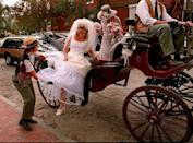 <p>The low scoop-neck of this 1996 bride feels more timeless than other looks of the era. The carriage attendant's ensemble, though, is decidedly '90s. </p>