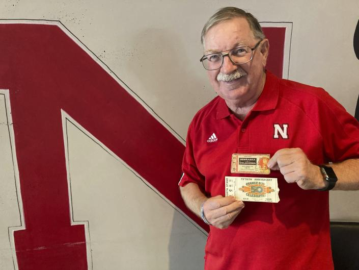 """John Fey shows off his ticket stubs from Nebraska's 1971 """"Game of the Century"""" against Oklahoma and the Cornhuskers' 1984 Orange Bowl against Miami on Aug. 6, 2021, in Papillion, Neb. Traditional tickets on cardstock began fading away in the last decade with the advent of print-at-home tickets and digital, or mobile, ticketing systems requiring fans to have a barcode on their smartphones scanned at the gate. (AP Photo/Eric Olson)"""