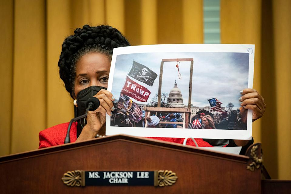 <p>Sheila Jackson Lee holds a photo of the crowd at the 6 January insurrection  during a House committee hearing on 24 February.</p> (Getty Images)
