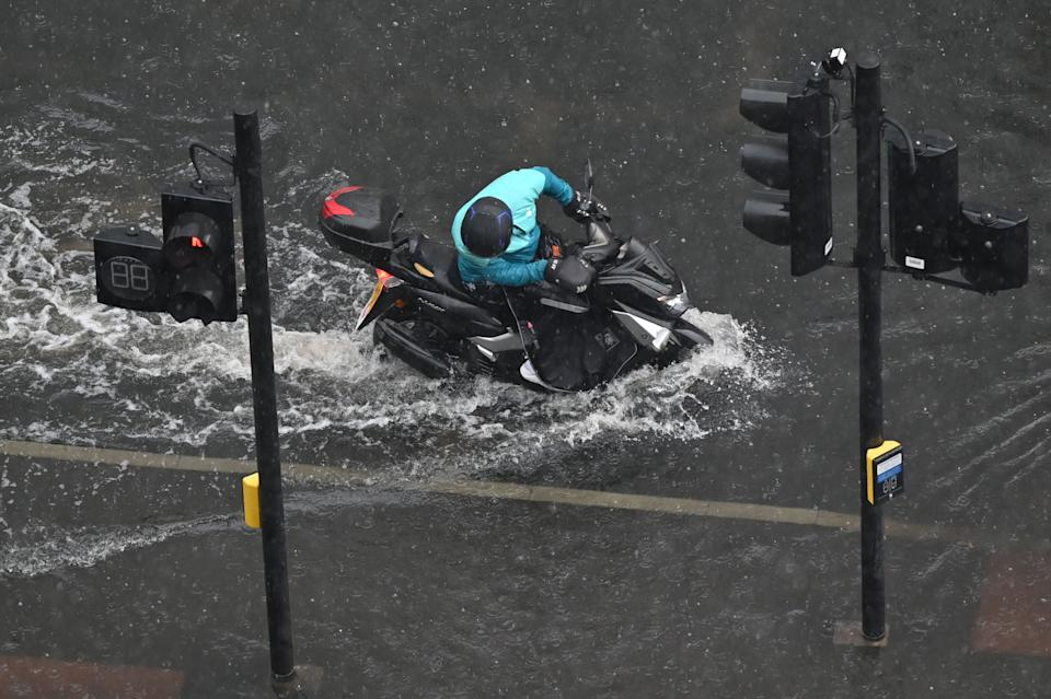 A motorcyclist tries to ride through deep water on a flooded road in The Nine Elms district of London on July 25, 2021 during heavy rain. - Buses and cars were left stranded when roads across London flooded on Sunday, as repeated thunderstorms battered the British capital. (Photo by JUSTIN TALLIS / AFP) (Photo by JUSTIN TALLIS/AFP via Getty Images)