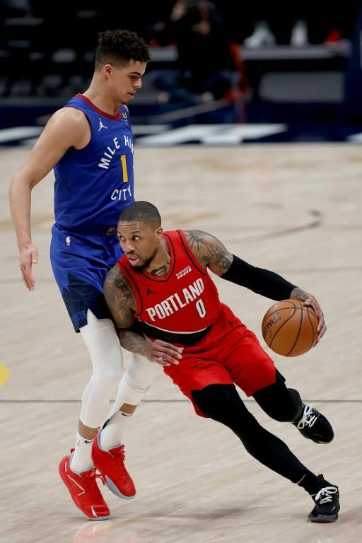 Damian Lillard drives around Michael Porter Jr. during Portland's playoff loss to the Denver Nuggets on Tuesday