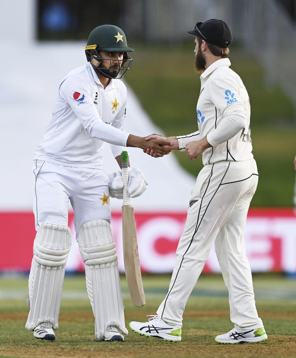 New Zealand captain Kane Williamson, right, congratulates Pakistan's Faheem Ashraf at the end of play after he scored 91 runs on day three of the first cricket test between Pakistan and New Zealand at Bay Oval, Mount Maunganui, New Zealand, Monday, Dec. 28, 2020. (Andrew Cornaga/Photosport via AP)