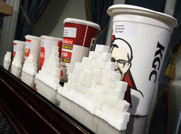 FILE - This Thursday, May 31, 2012 file photo shows a display of various size soft drink cups next to stacks of sugar cubes at a news conference at New York's City Hall. New research greatly strengthens the case against soda and other sugary drinks as culprits in the obesity epidemic. Two major experiments found that children and teens gained less weight when they regularly drank calorie-free beverages instead of sugary ones. A third study gives the first clear evidence that consuming sugary drinks interacts with genes that affect weight. Scientists say the results add weight to the push for taxes, size limits and other policies to curb consumption. (AP Photo/Richard Drew, File)
