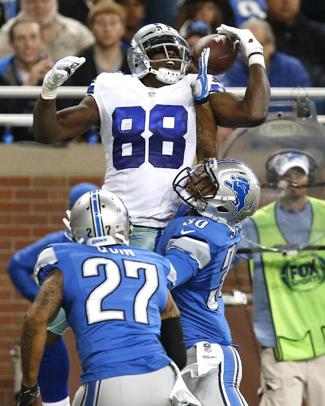Dallas Cowboys wide receiver Dez Bryant (88) catches a 5-yard touchdown reception as Detroit Lions cornerback Darius Slay (30) defends and Glover Quin watches in the second quarter of an NFL football game in Detroit, Sunday, Oct. 27, 2013. (AP Photo/Duane Burleson)