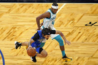 Orlando Magic guard Cole Anthony, left, is tripped up by Charlotte Hornets guard Devonte' Graham (4) as he drives downcourt during the second half of an NBA basketball game, Sunday, Jan. 24, 2021, in Orlando, Fla. (AP Photo/John Raoux)