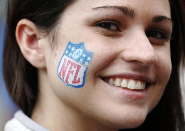 Mikaela Brady of Buffalo, U.S., poses with the NFL logo painted on her face during a 'block party' on London's Regent Street ahead of the Pittsburgh Steelers versus the Minnesota Vikings and San Francisco 49ers versus the Jacksonville Jaguars NFL matches in London September 28, 2013. REUTERS/Luke MacGregor (BRITAIN - Tags: SPORT SOCIETY HEADSHOT)