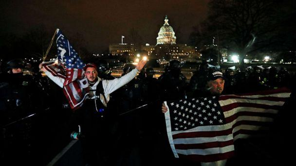 PHOTO: Supporters of President Donald Trump hold U.S. flags as they walk next to police near the Capitol during a protest against the certification of the 2020 U.S. presidential election results by the congress, Jan. 6, 2021. (Jim Bourg/Reuters)