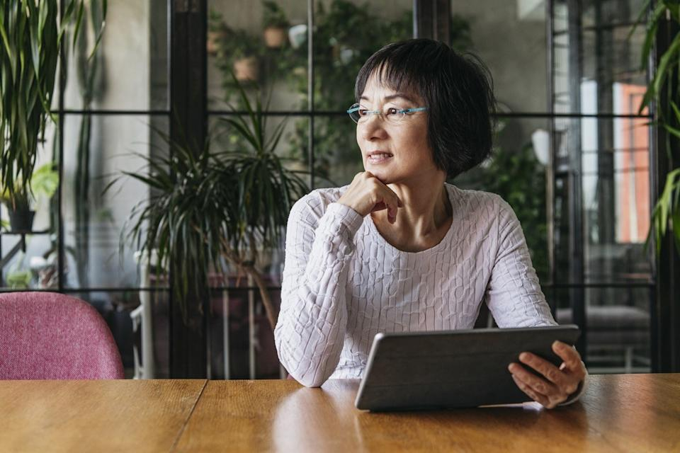 Thoughtful senior woman sitting at home with digital device, looking away and daydreaming