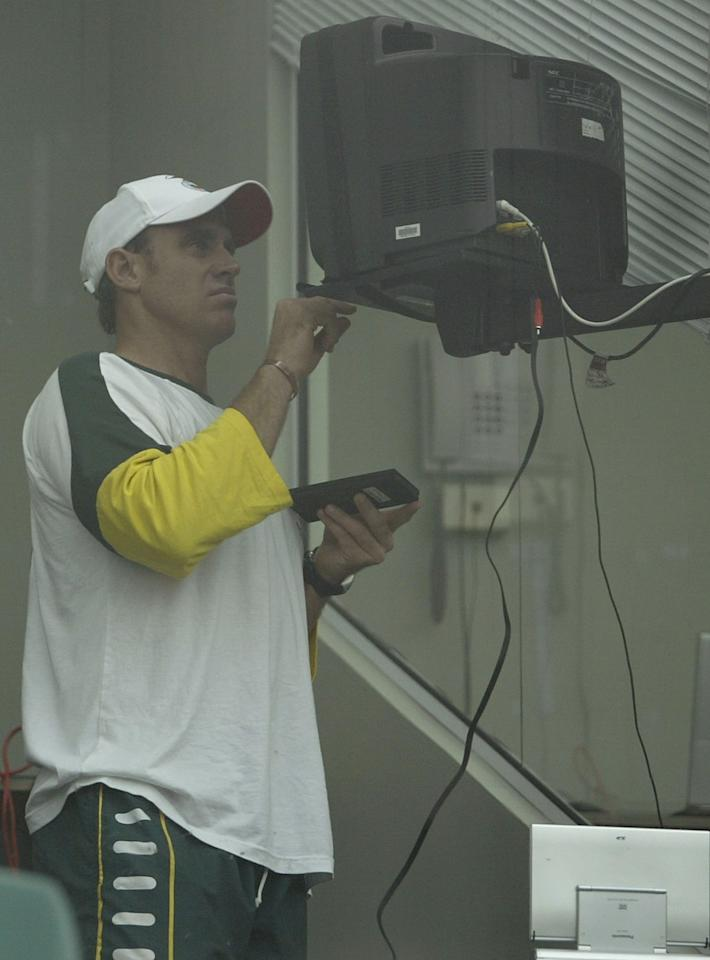 BRISBANE, AUSTRALIA - DECEMBER 5:  Matthew Hayden of Australia adjust the television set in the players room as he waits for rain to clear and play to start on day two of the first test between Australia and India played December 5, 2003 at the Gabba in Brisbane, Australia.  (Photo by Chris McGrath/Getty Images)