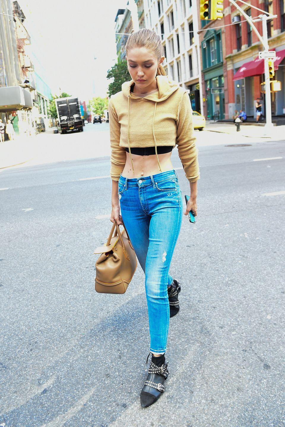 <p>Hadid wears a cropped beige sweatshirt over a crop top, distressed jeans, studded pointed-toe ankle boots and a Versace Palazzo Empire bag. </p>