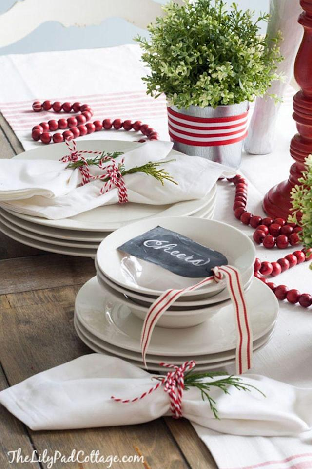 """<p>Keep things simple with a classic red and white theme. Strands of red beads mimic the festive look of cranberries, while a simple grosgrain ribbon dresses up a planter.</p><p><strong>Get the tutorial at <a href=""""http://www.thelilypadcottage.com/2014/12/classic-christmas-tour.html"""" rel=""""nofollow noopener"""" target=""""_blank"""" data-ylk=""""slk:The Lily Pad Cottage"""" class=""""link rapid-noclick-resp"""">The Lily Pad Cottage</a>.</strong></p><p><strong><a class=""""link rapid-noclick-resp"""" href=""""https://www.amazon.com/Grosgrain-Accessories-Scrapbooking-Packaging-Decoration/dp/B07LC8WRPP?tag=syn-yahoo-20&ascsubtag=%5Bartid%7C10050.g.644%5Bsrc%7Cyahoo-us"""" rel=""""nofollow noopener"""" target=""""_blank"""" data-ylk=""""slk:SHOP RED AND WHITE RIBBON"""">SHOP RED AND WHITE RIBBON</a><br></strong></p>"""