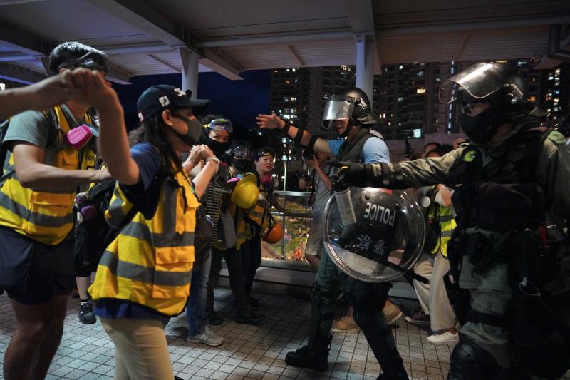 People to block policemen who arrive to arrest protesters at Tung Chung near airport in Hong Kong, Sunday, Sept.1, 2019. Train service to Hong Kong's airport was suspended Sunday as pro-democracy demonstrators gathered there, while protesters outside the British Consulate called on London to grant citizenship to people born in the former colony before its return to China. (AP Photo/Vincent Yu)