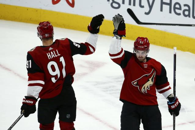 Arizona Coyotes right wing Conor Garland (83) celebrates his empty net goal against the San Jose Sharks with Coyotes left wing Taylor Hall (91) during the third period of an NHL hockey game Tuesday, Jan. 14, 2020, in Glendale, Ariz. The Coyotes defeated the Sharks 6-3. (AP Photo/Ross D. Franklin)