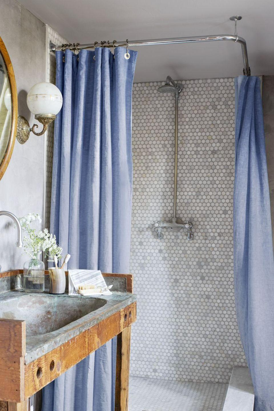 <p>Penny tiles create a focal point against the cornflower blue shower curtains in this charming bathroom filled with subdued shades of gray.<br></p>