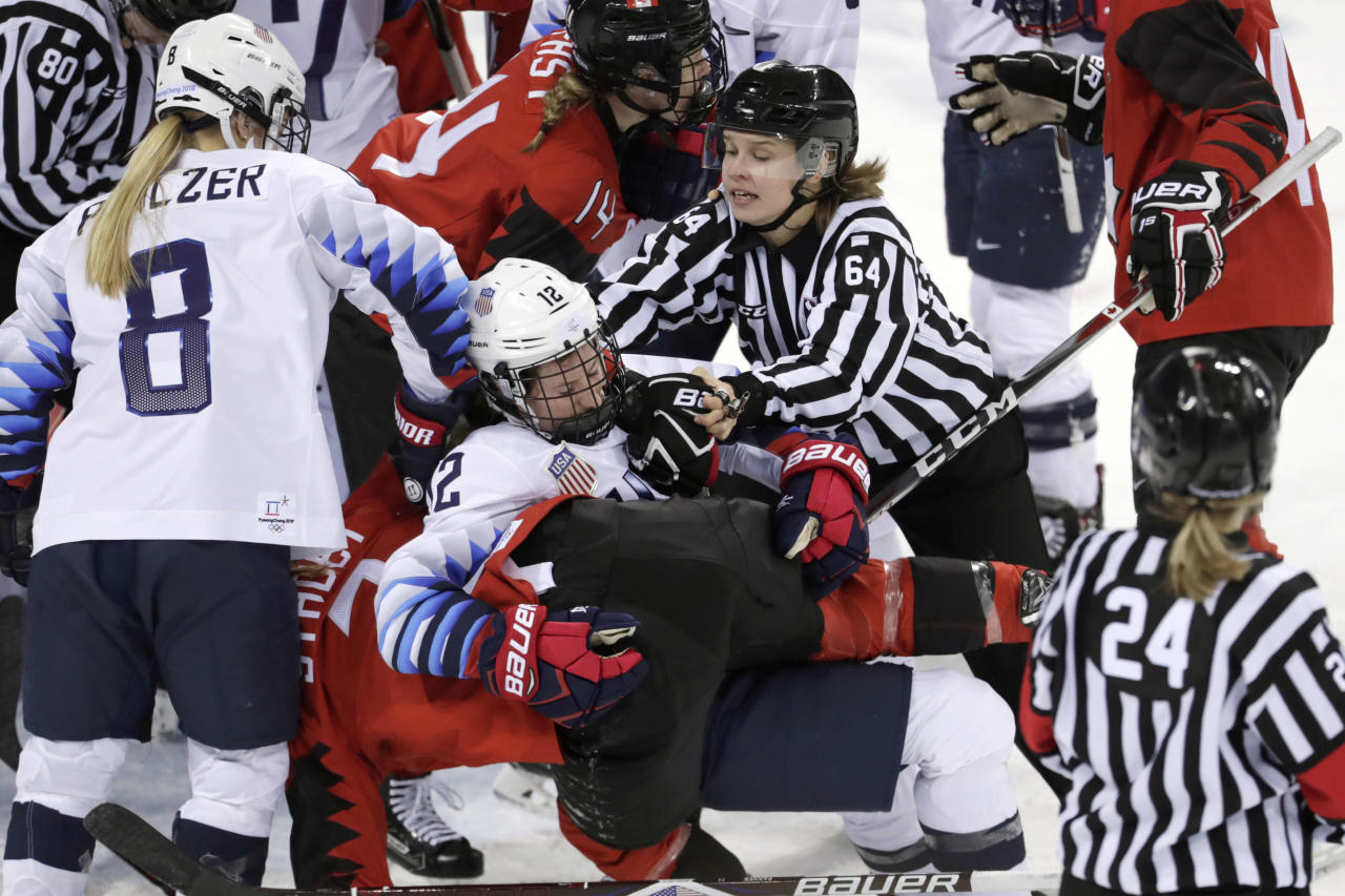 <p>Official Jenni Heikkinen (64), of Finland, tries to separate Kelly Pannek (12), of the United States, and Laura Stacey (7), of Canada, as they scuffle during the third period of a preliminary round during a women's hockey game at the 2018 Winter Olympics in Gangneung, South Korea, Thursday, Feb. 15, 2018. Canada won 2-1. (AP Photo/Julio Cortez) </p>