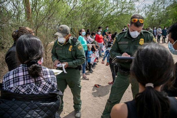 PHOTO: U.S. Border Patrol agents question asylum seekers after their group of immigrants crossed the Rio Grande into Texas on March 25, 2021, in Hidalgo, Texas. (John Moore/Getty Images)