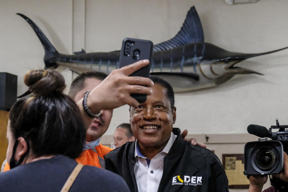 Republican conservative radio show host Larry Elder takes photos with patrons when he visiting Philippe The Original Deli during a campaign for the California gubernatorial recall election on Monday, Sept. 13, 2021, in Los Angeles. (AP Photo/Ringo H.W. Chiu)