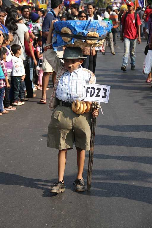 A child participates in the Goa Carnival parade dressed as a local bread (pao) seller.