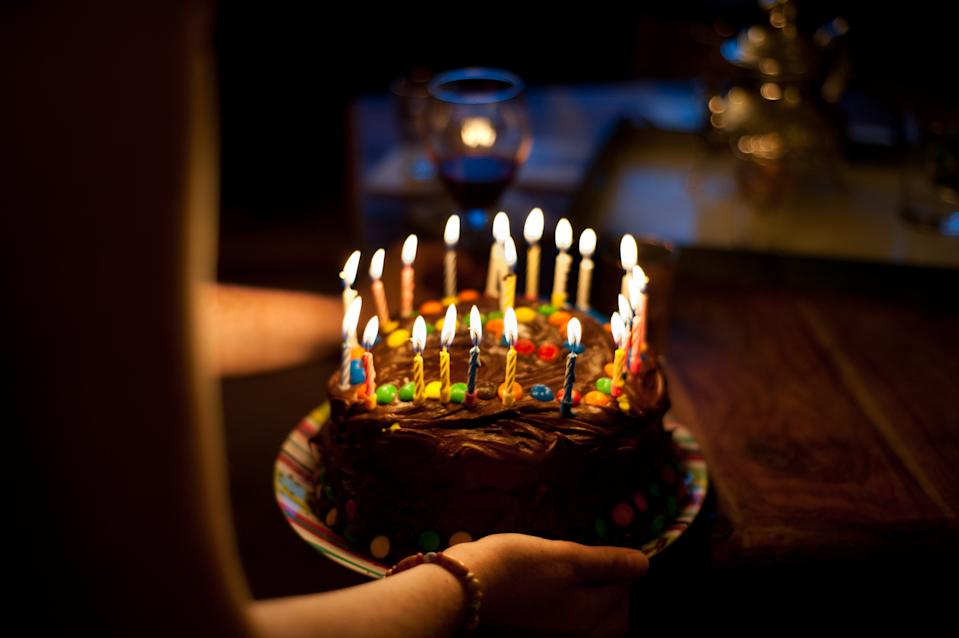 A person holding a birthday cake.