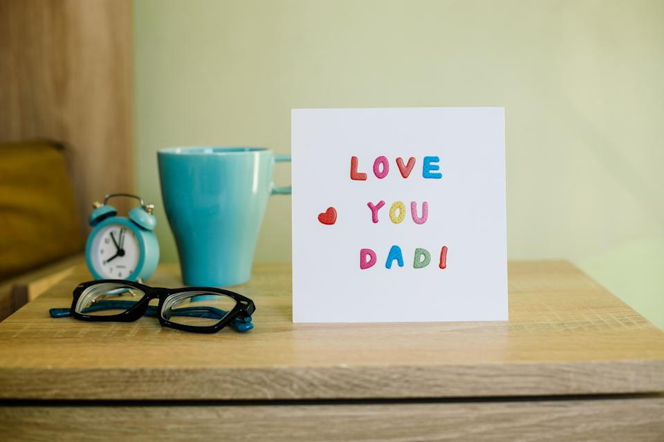 Greeting Card for Happy Father's Day, on the bed, paper white sheet with text Love You Dad and heart, colorful letters