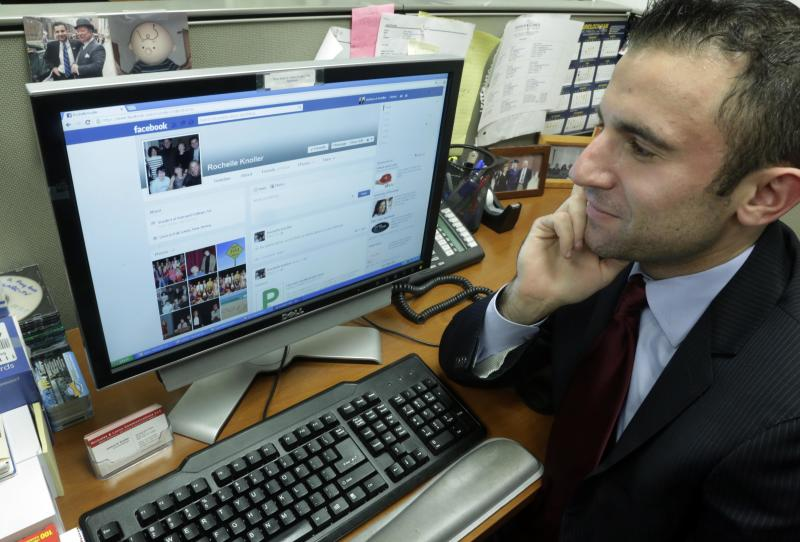 "Joshua Knoller, an account manager with Nicholas & Lence Communications, looks at the Facebook page of his mother, Rochelle Knoller of Fair Lawn, N.J., on his office computer, in New York,  Thursday, May 9, 2013. Knoller spent years refusing his mother's ""Friend Request"" on Facebook before eventually ""caving in."" Today they have an agreement: she'll try not to make embarrassing comments, and he can delete them if she does.(AP Photo/Richard Drew)"