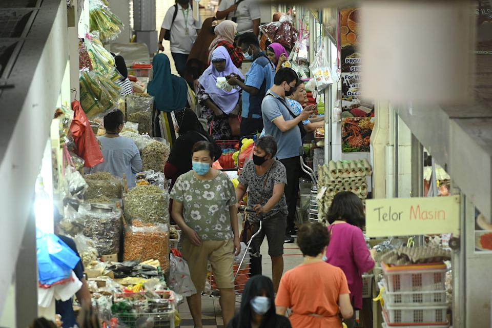 People, wearing face masks as a preventive measure against the spread of the COVID-19 novel coronavirus, shop for food items in the Geylang Serai market in Singapore on April 8, 2020. (Photo by Roslan RAHMAN / AFP) (Photo by ROSLAN RAHMAN/AFP via Getty Images)