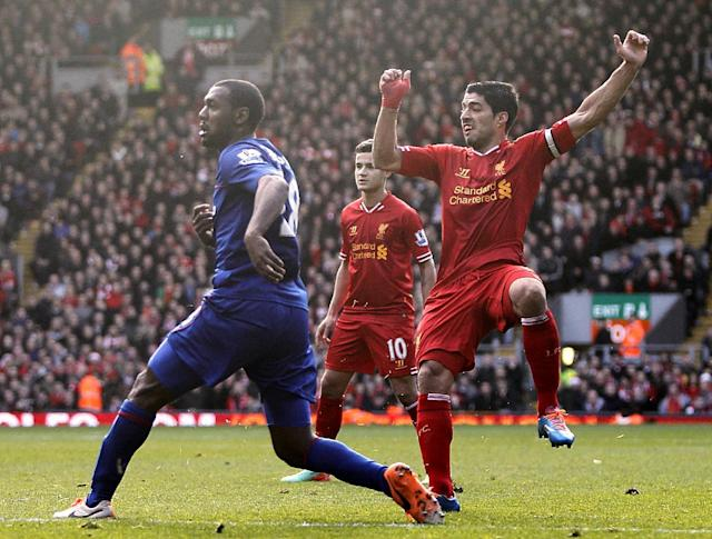 Liverpool's Luis Suarez, right, scores his team's third goal during their English Premier League soccer match against Cardiff City at Anfield, Liverpool, England, Saturday, Dec. 21, 2013. (AP Photo/Peter Byrne, PA Wire) UNITED KINGDOM OUT - NO SALES - NO ARCHIVES