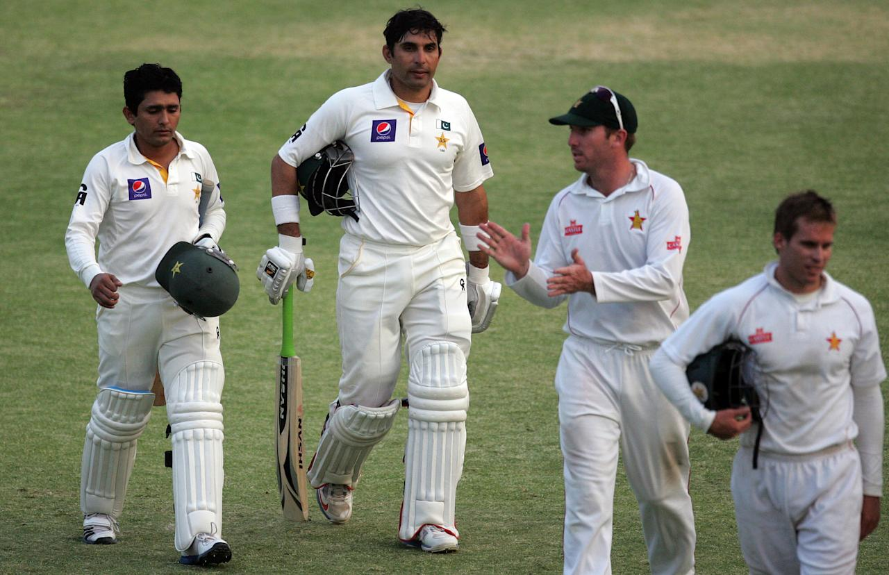 Pakistan's batsman Adnan Akmal (L) and captain Misbah-Ul-Haq (C) walk off the pitch along with Zimbabwe's captain Brendan Taylor and Malcolm Waller (R) at the end of the fourth day of the second test match between Pakistan and Zimbabwe at the Harare Sports Club on September 13, 2013. AFP PHOTO / JEKESAI NJIKIZANA        (Photo credit should read JEKESAI NJIKIZANA/AFP/Getty Images)