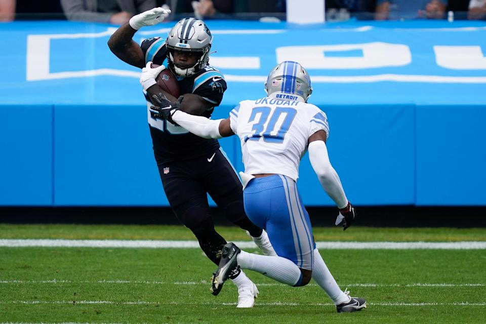 Panthers running back Mike Davis runs past Lions cornerback Jeff Okudah during the first half on Sunday, Nov. 22, 2020, in Charlotte, N.C.