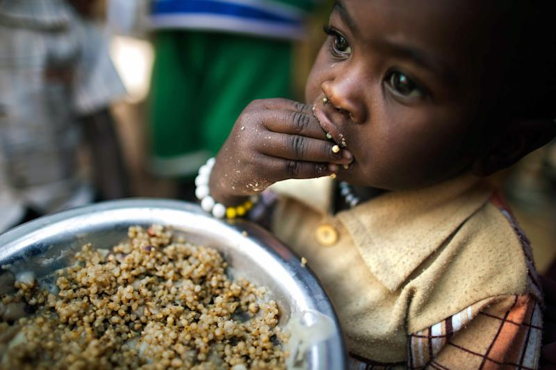 A child eats lentils in a food distribution centre on March 4, 2014, at a camp for internally displaced people in Tawila, North Darfur (AFP Photo/Albert Gonzalez Farran)