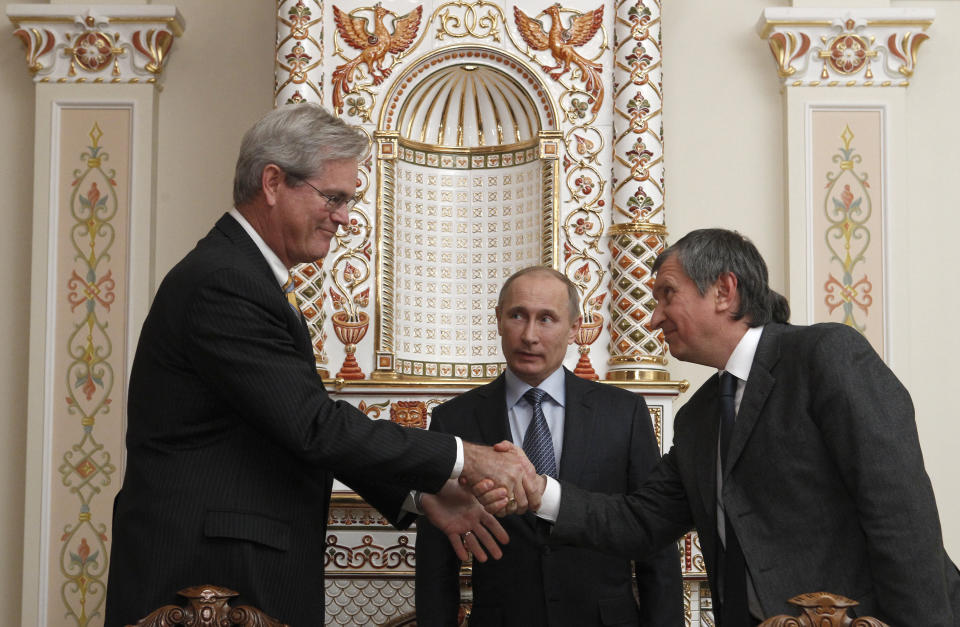 <p> CEO of state-controlled Russian oil company Rosneft Igor Sechin, right, and President of ExxonMobil Exploration Company Stephen Greenlee shake hands after signing document with Russian President Vladimir Putin, center, attending the signing ceremony, in the Novo-Ogaryovo residence outside Moscow, Wednesday, Feb. 13, 2013. (AP Photo/Sergei Karpukhin, Pool) </p>